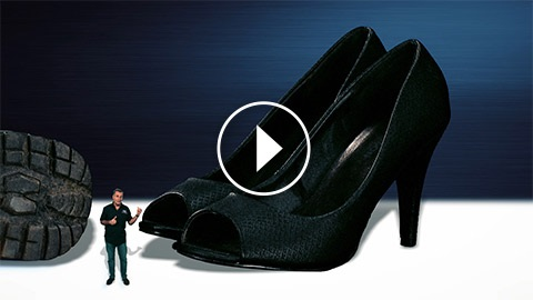 Small man pointing to giant womens black high heeled shoes.